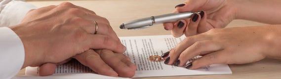 Vrouw en echtgenoot die scheidingsdocumenten of voorhuwelijkse overeenkomst ondertekenen royalty-vrije stock fotografie