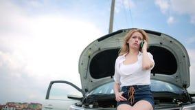 Vrouw en gebroken auto die hulp op celtelefoon verzoeken Gebroken auto op de weg stock videobeelden