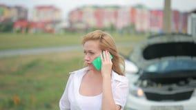 Vrouw en gebroken auto die hulp op celtelefoon verzoeken Gebroken auto op de weg stock footage