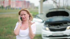 Vrouw en gebroken auto die hulp op celtelefoon verzoeken Vrouw het schreeuwen stock videobeelden