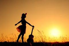 Vrouw en gitaar met zonsondergangsilhouet Royalty-vrije Stock Foto's