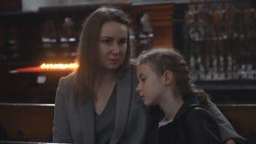 Vrouw en haar dochter in de kerk stock footage