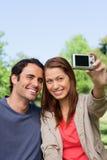 Vrouw en haar vriend die naar haar camera voor een beeld kijken van Stock Foto