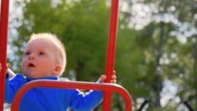 Vrouw en haar weinig zoon die een schommeling op de speelplaats spelen bij het park stock videobeelden
