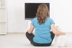 Vrouw en hond die op TV samen letten royalty-vrije stock afbeeldingen