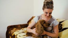 Vrouw en hondcocker-spaniël Hij strijkt, raakt, koestert, kust, glimlacht stock videobeelden