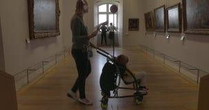 Vrouw en jong geitje die in zalen van Louvremuseum lopen stock footage