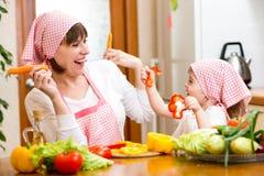 Vrouw en jong geitje het meisje heeft pret het koken in keuken Stock Fotografie