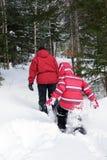 Vrouw en jong geitje het snowshoeing Royalty-vrije Stock Afbeeldingen