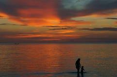 Vrouw en jong geitje in zonsondergang Royalty-vrije Stock Foto's