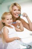 Vrouw en jong meisje in badkamers het borstelen tanden stock afbeeldingen
