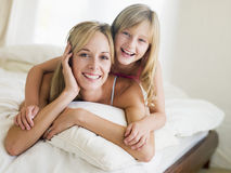 Vrouw en jong meisje die in bed het glimlachen liggen Royalty-vrije Stock Afbeeldingen