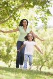 Vrouw en jong meisje die in openlucht het glimlachen in werking stellen Stock Fotografie