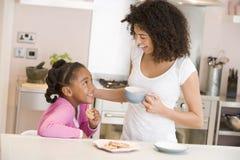 Vrouw en jong meisje in keuken met koekjes en c royalty-vrije stock foto's