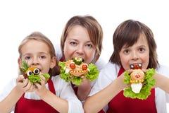 Vrouw en jonge geitjes die een beet van creatieve sandwiches nemen royalty-vrije stock foto