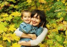 Vrouw en jongen in de bladeren Royalty-vrije Stock Foto's