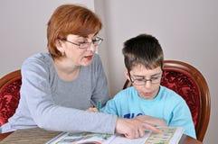 Vrouw en jongen die thuiswerk doen Stock Foto