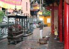 Vrouw en Kind die bij Boeddhistische Tempel bidden Stock Foto