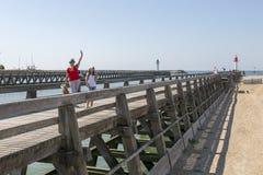 Vrouw en kind die bij de pijler van Trouville golven stock fotografie