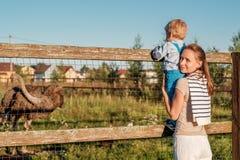 Vrouw en kind die bij landbouwbedrijf struisvogel bekijken Royalty-vrije Stock Fotografie