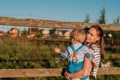 Vrouw en kind die bij landbouwbedrijf struisvogel bekijken Royalty-vrije Stock Afbeeldingen