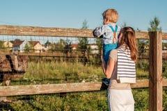 Vrouw en kind die bij landbouwbedrijf struisvogel bekijken Stock Foto's