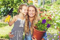 Vrouw en kind die bij tuin werken stock afbeelding