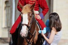 vrouw en kind die een rood paard strijken waarop de ruiter zit, gekleed in periodekostuum Stock Foto
