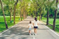 Vrouw en kind die op voetpad en gang in het openbare park lopen royalty-vrije stock foto's
