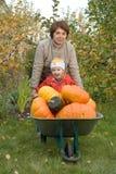 Vrouw en kind in een tuin Stock Afbeeldingen