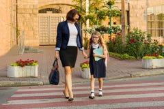 Vrouw en kind - handen van een de jonge schoolmeisjeholding, bij de gestreepte kruising royalty-vrije stock foto's