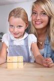 Vrouw en kind het spelen domino's royalty-vrije stock afbeeldingen