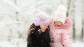 Vrouw en kind het spelen met sneeuw in de winter stock footage