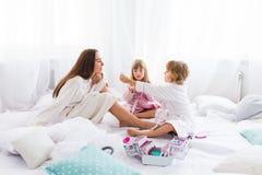 Vrouw en kinderen op bed Stock Afbeeldingen
