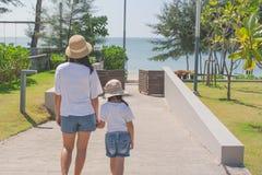 Vrouw en kindholdingshand samen en lopend aan zandstrand stock foto's