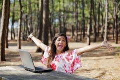 Vrouw en laptop in pijnboombos Royalty-vrije Stock Afbeeldingen