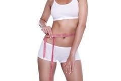 Vrouw en maatregelenband rond haar lichaam stock fotografie