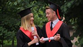 Vrouw en man in academische kleding die diploma's houden, en in park spreken lopen stock videobeelden