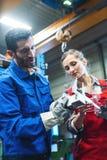 Vrouw en man arbeider die metingen van het stuk van het metaalwerk controleren royalty-vrije stock afbeelding