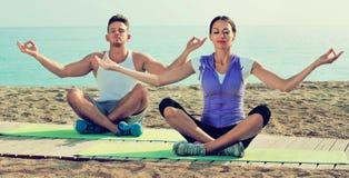 Vrouw en man de zitting doet met de benen over elkaar yoga stelt op strand Royalty-vrije Stock Foto's