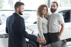 Vrouw en man die auto met autohandelaar waarnemen stock afbeelding