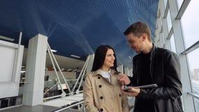 Vrouw en man die en tablet binnen de luchthavenbouw lachen bekijken stock video