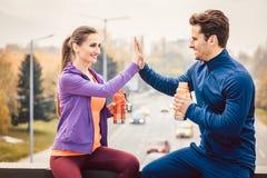 Vrouw en man die hallo-vijf na fitness sport in een stad geven stock afbeelding