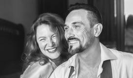 Vrouw en man die pret samen, in eigen ruimte hebben Vrouw die de camera, een man in de zwart-witte rechterkant onderzoeken Stock Fotografie