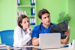 Vrouw en man gynaecologen die medisch geval bespreken bij clini stock afbeeldingen