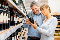 Vrouw en man het kopen wijn in supermarkt royalty-vrije stock foto's