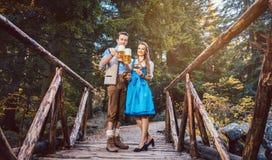 Vrouw en man met bier die zich op brug in Beieren bevinden royalty-vrije stock afbeelding