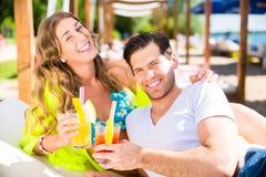 Vrouw en man met dranken in strandbar stock foto