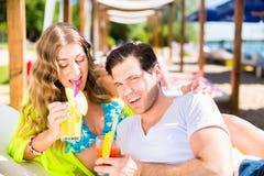Vrouw en man met dranken in strandbar royalty-vrije stock fotografie