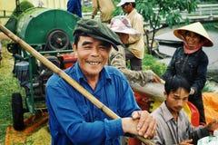 vrouw en man oogstende en gietende rijstzaden aan een plastic zak met een mobiele dorsmachine op de achtergrond stock foto